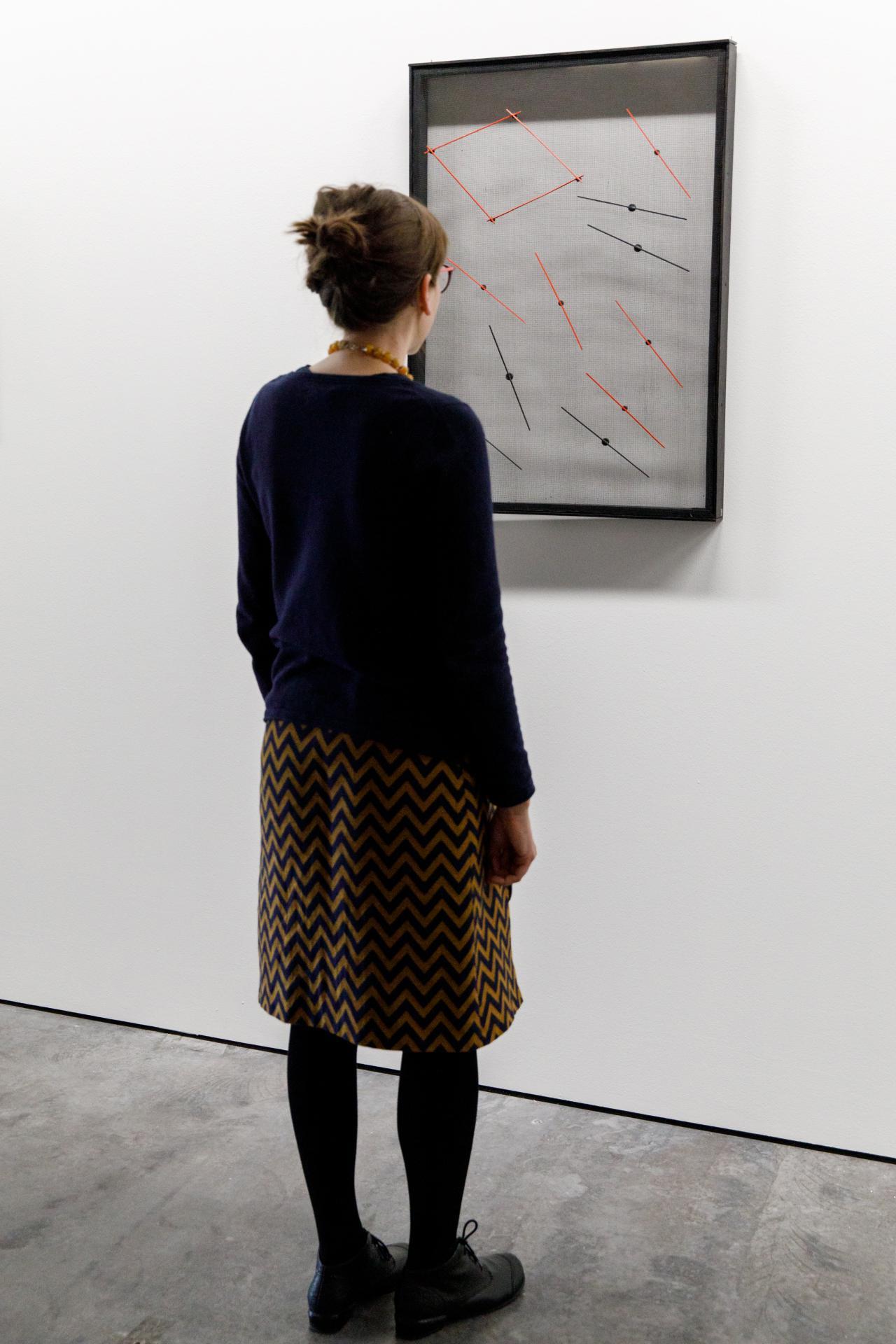 Besucherin vor einem Werk der Ausstellung »Writing the History of the Future«