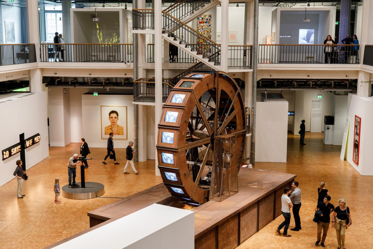 A huge metal mill wheel stands in an exhibition room. At the mill wheel there are tube screens on which videos of water are played.