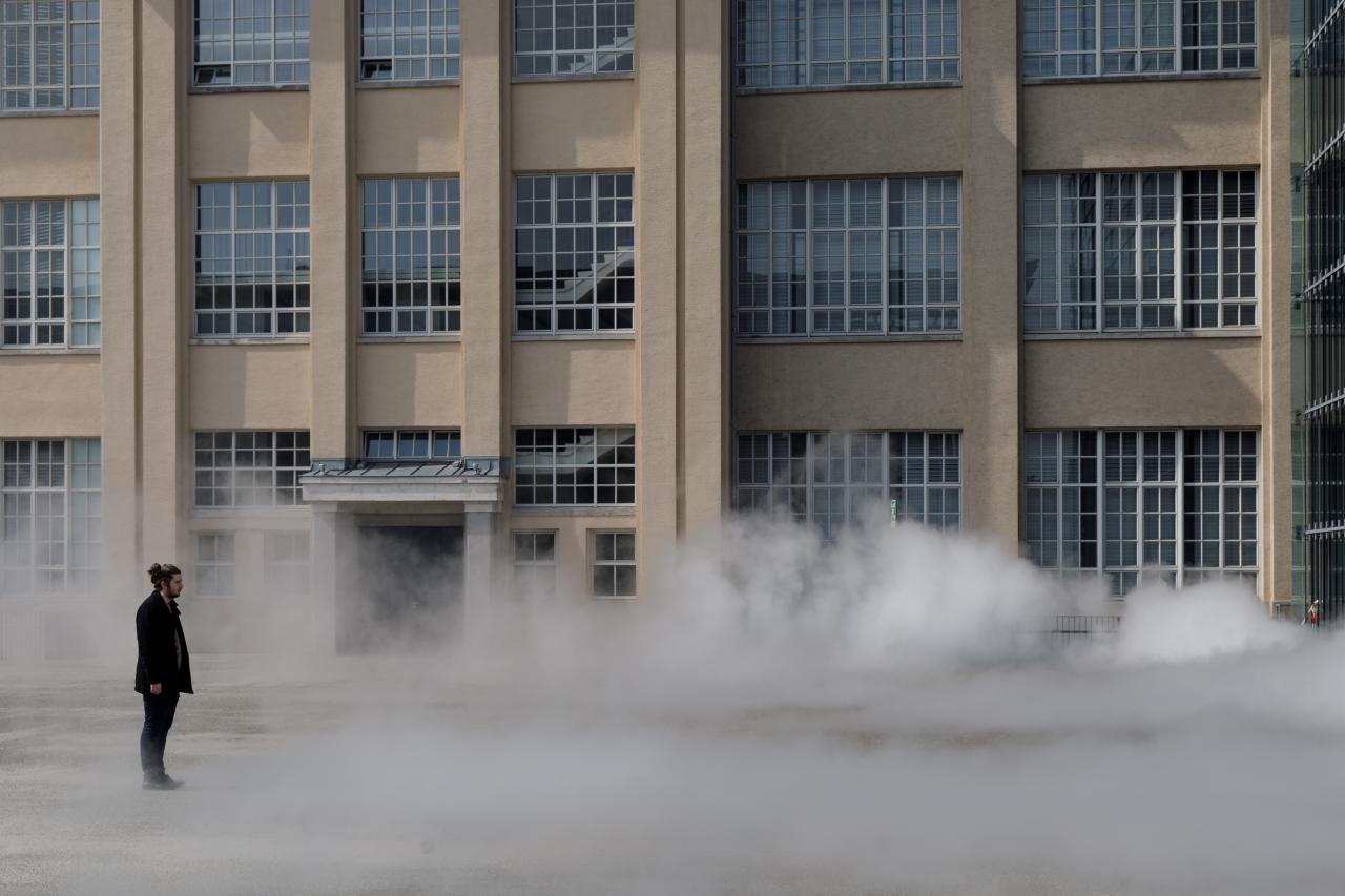 Das Foto zeigt einen Mann ummantelt von der Nebelskulptur der japanischen Künstlerin Fujiko Nakaya. Im Hintergrund ist die Fassade der alten Munitionsfabrik zu sehen.