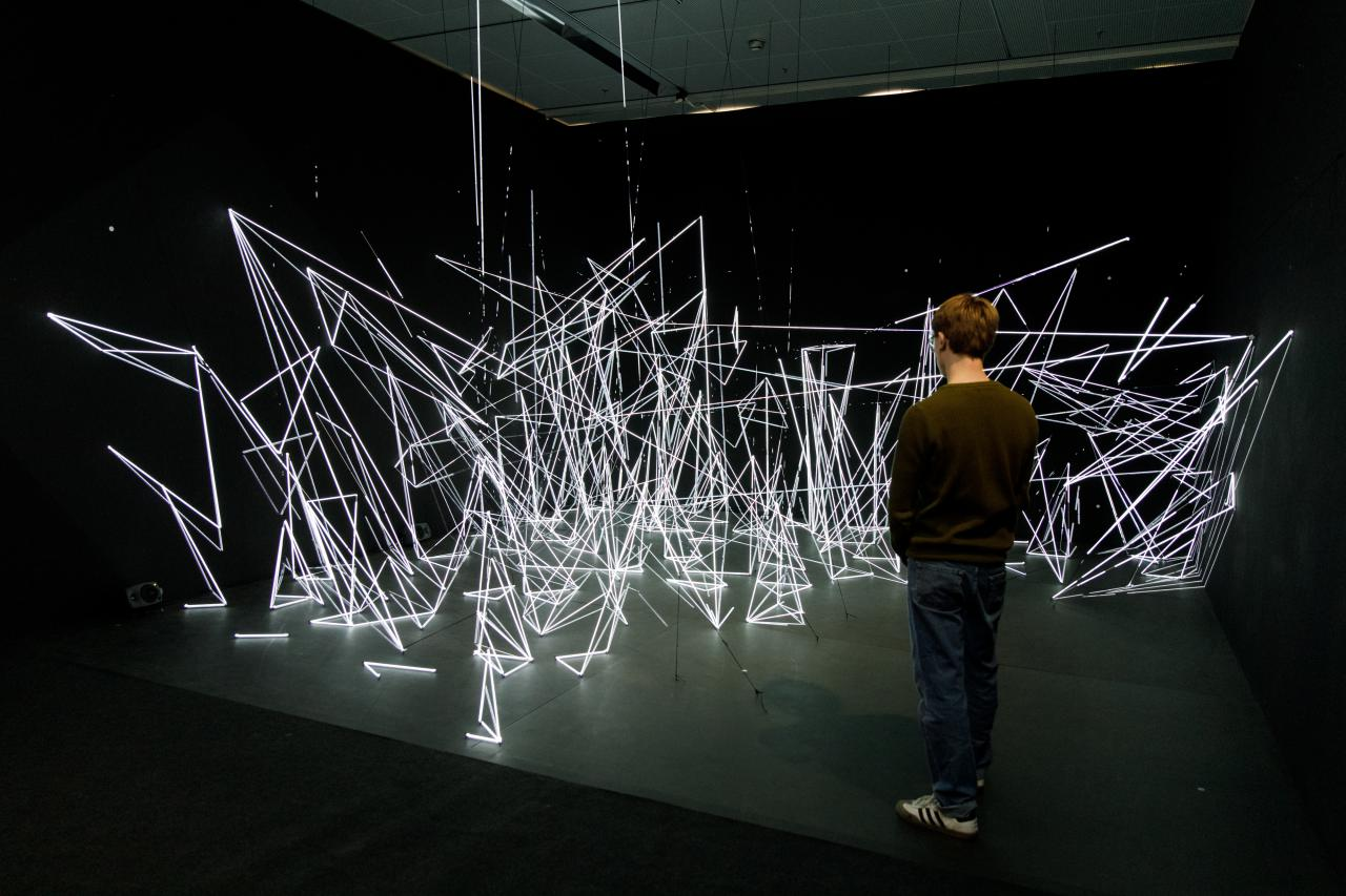 An installation of white, illuminated nylon threads in geometric shapes.