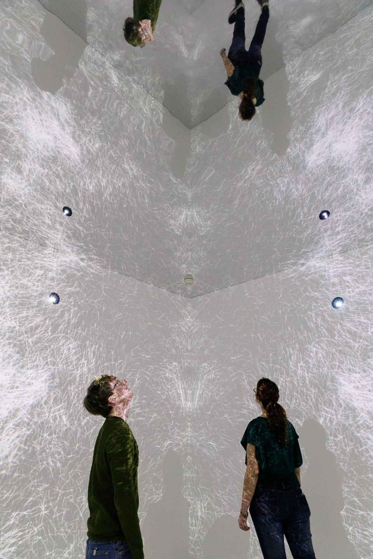 Visitors in a room with video projections on walls and ceiling and a mirrored floor.