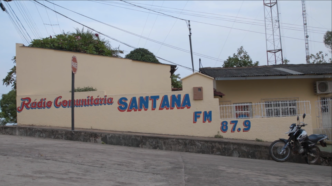 "You can see a wall of a house which says ""Radio Comunitaria Santana FM 87.9""."