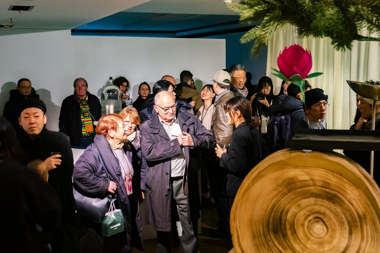 Zu sehen sind viele Menschen in der Galerie damdam in Berlin. Auf der rechten Seite des Bildes erscheint verschwommen ein Tannenzweig darunter ist eine große Rote Papierblüte zu sehen.