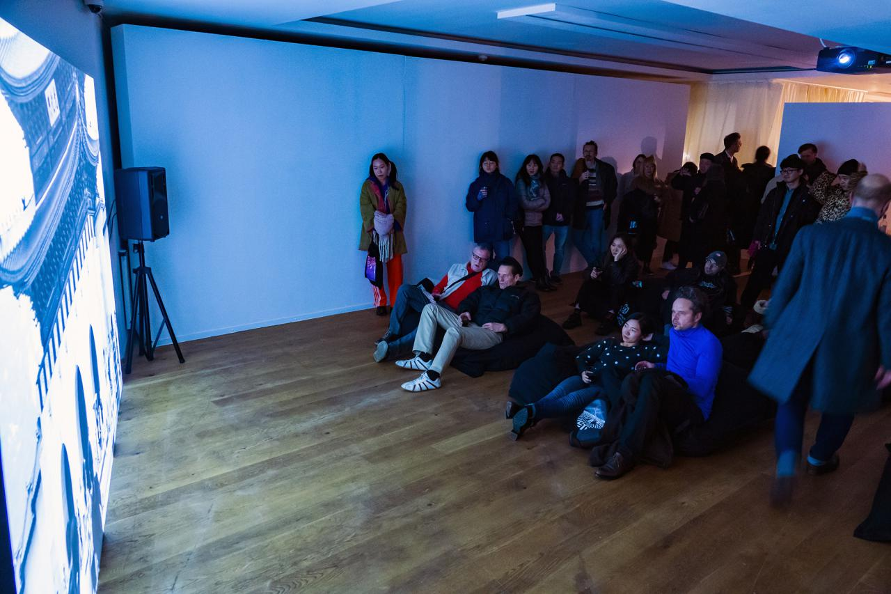 Zu sehen sind viele Menschen die vor einer großen Kunstprojektion stehen oder liegen. Der Raum hat einen Holzboden und wird von der Projektion blau erleuchtet.