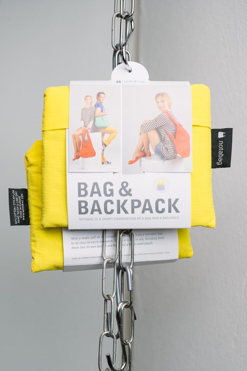Eine Kombination aus Tasche und Rucksack, faltbar, gelb, an einer Eisenkette aufgehängt