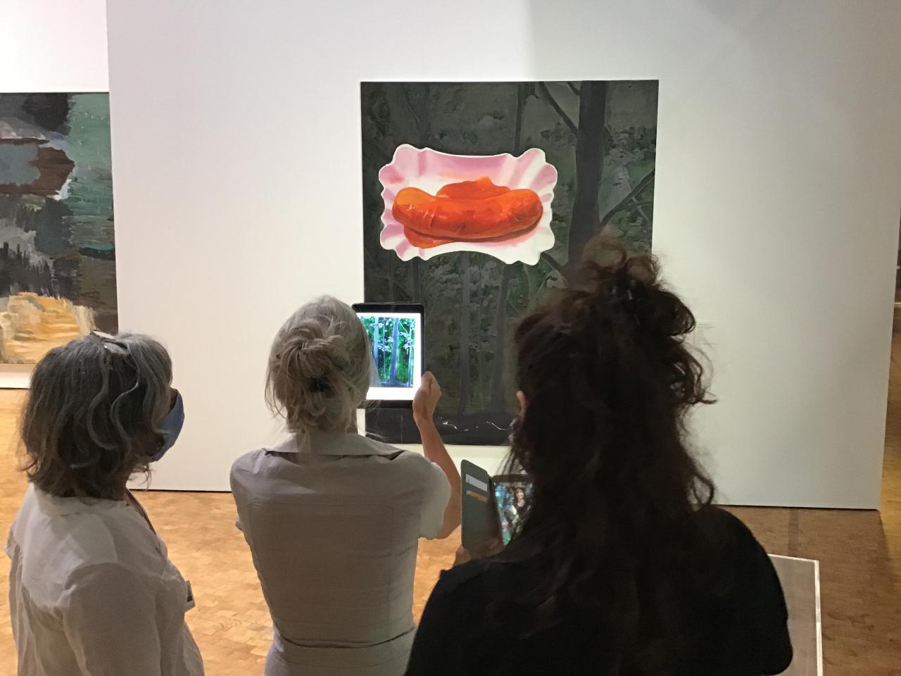 Drei Frauen stehen vor einem Bild, auf dem eine Currywurst in einer Pappschale zu sehen ist. Eine der Frauen hält ein iPad auf das Bild.