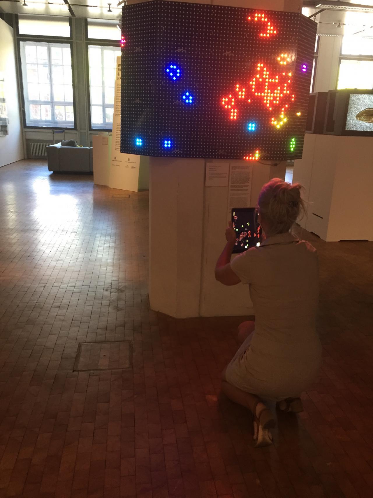 Zu sehen ist eine Frau, die vor einem Bildschirm kniet. In ihrer Hand hält sie ein iPad, das sie auf den Bildschirm gerichtet hast. Auf dem Bildschirm sind eingefärbte Pixelstrukturen zu erkennen.