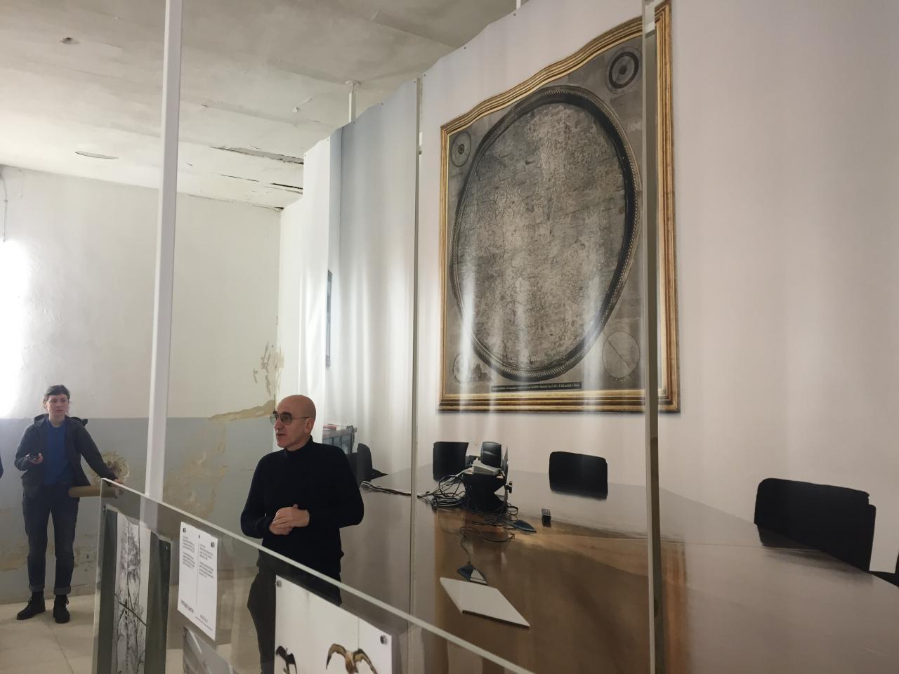 Ein Mann steht vor einer großformatigen Fotografie mit einer Karte über einem Schreibtisch.
