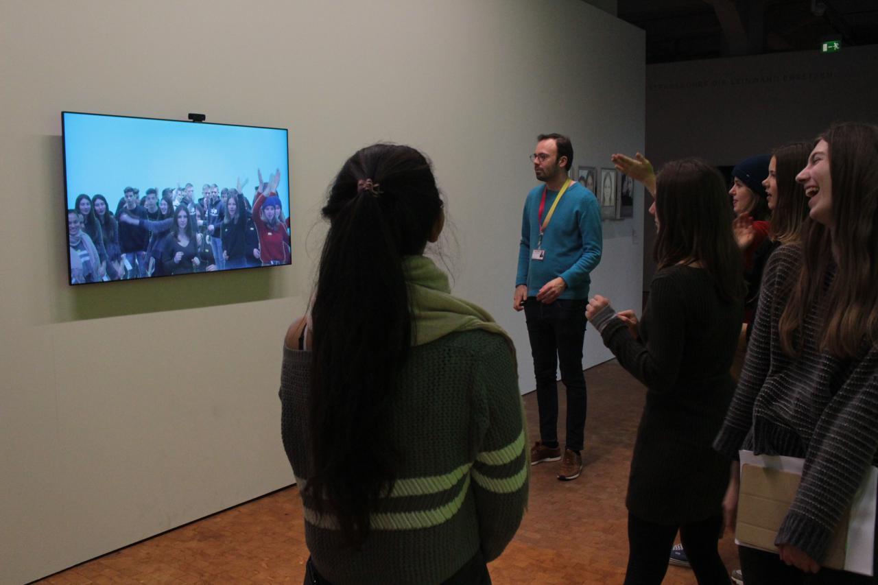 Zu sehen ist eine Gruppe an jungen Menschen, die vor einem Bildschirm stehen. Auf dem Bildschirm ist ein Live-Bild von der Gruppe zu sehen, das von einer Kamera über dem Bildschirm aufgenommen wird.