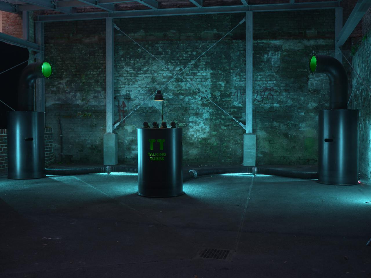 Ein blau erleuchteter Raum mit der Talking-Tubes-Installation: ein Steuerungspult zwischen zwei großen Röhren
