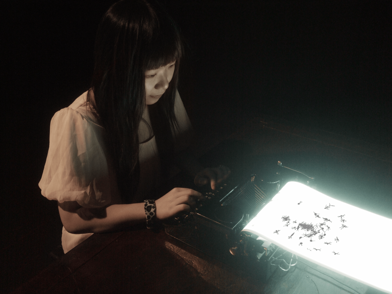 A woman is typing on a glowing typewriter