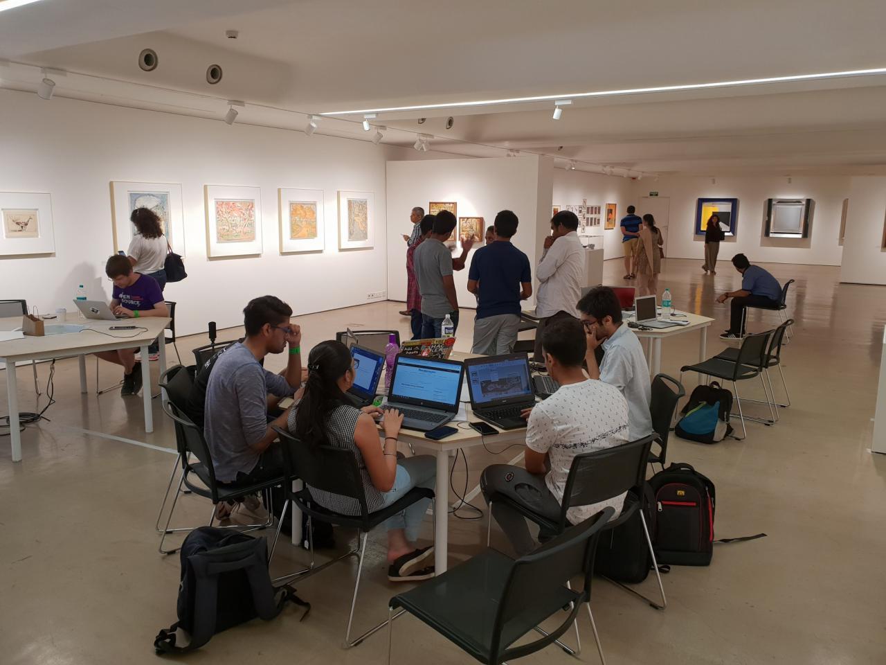 Eine Gruppe junger Menschen sitzt vor ihren Laptops an einem Tisch