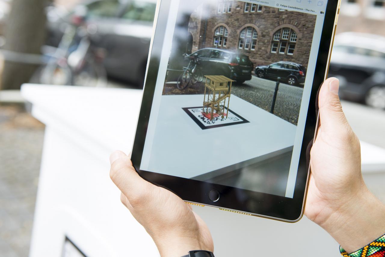 Auf einem Tablet-Bildschirm ist eine virtuelle Skulptur zu sehen, den realen Raum eingebettet ist.