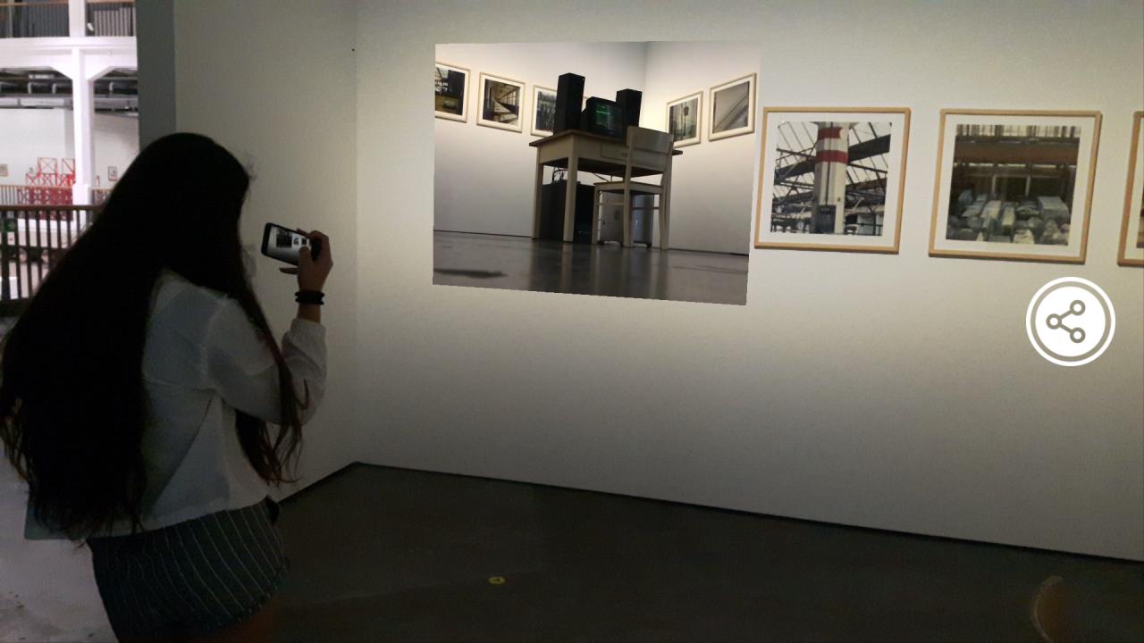 Ein Mädchen steht mit ihrem Handy in der Hand vor einem Bild. Sie hält ihr Handy so als würde sie das Bild filmen.