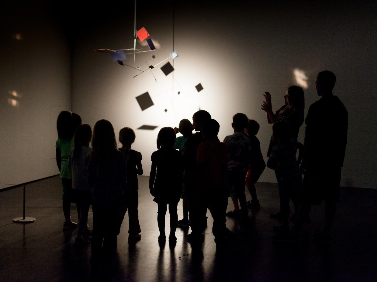 im dunkeln Museum stehende Kinder betrachten ein Mobile, das vom Licht angestrahlt wird