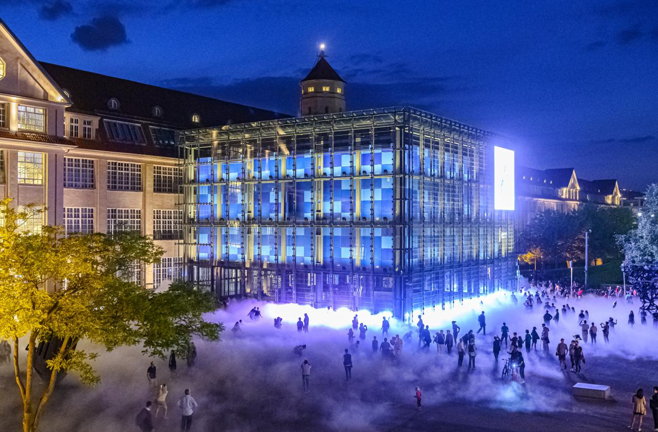 A large glass building - the cube of the ZKM Karlsruhe - is surrounded by fog. The photo was taken at night.