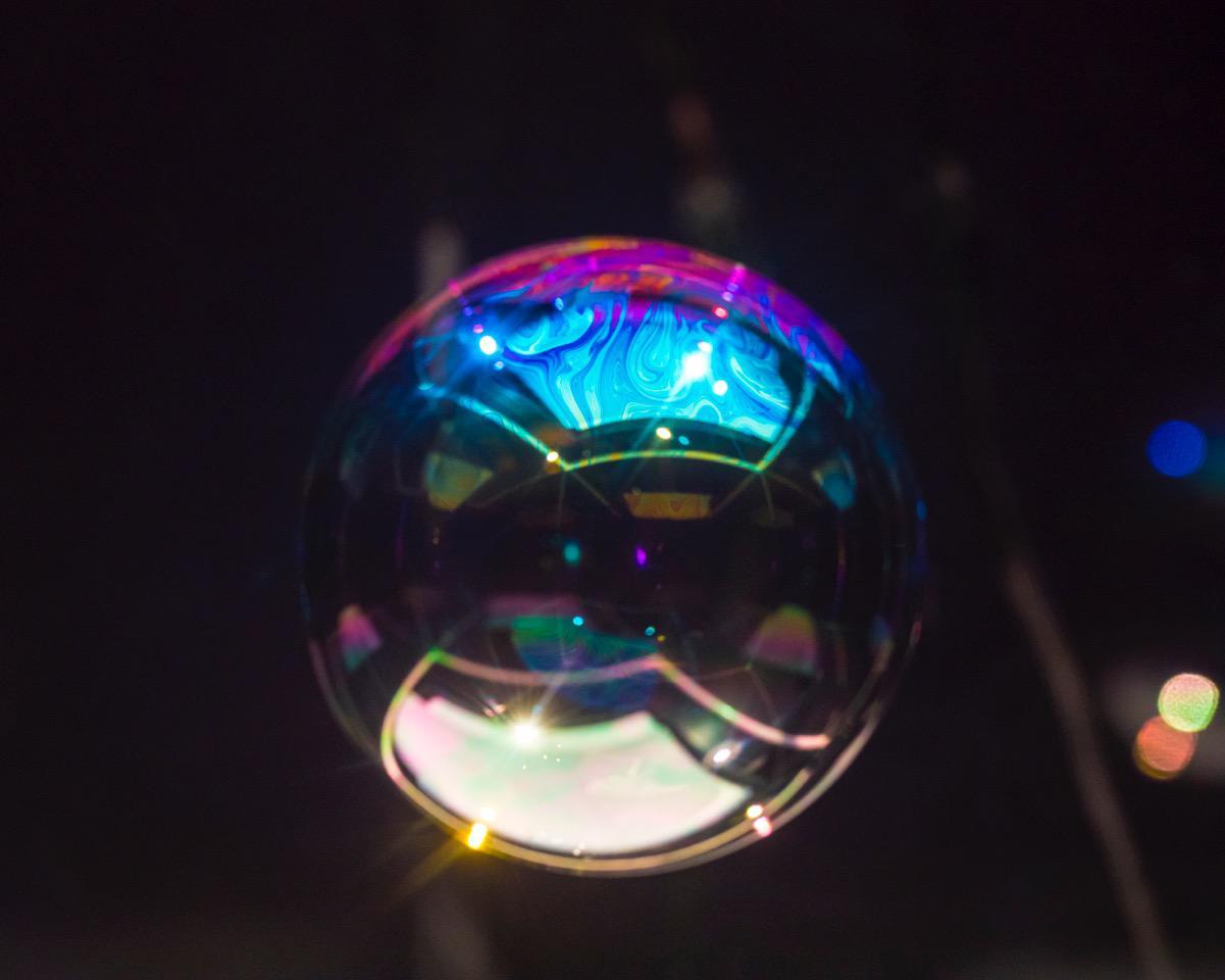 Das Foto zeigt eine Kugel ähnlich einer riesengroßen Seifenblase vor schwarzem Hintergrund