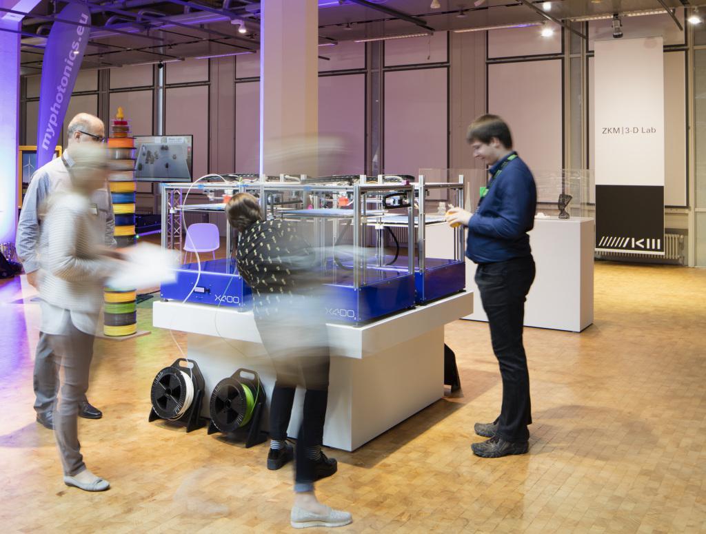 Vier 3D-Drucker vor denen Menschen stehen und zuschauen