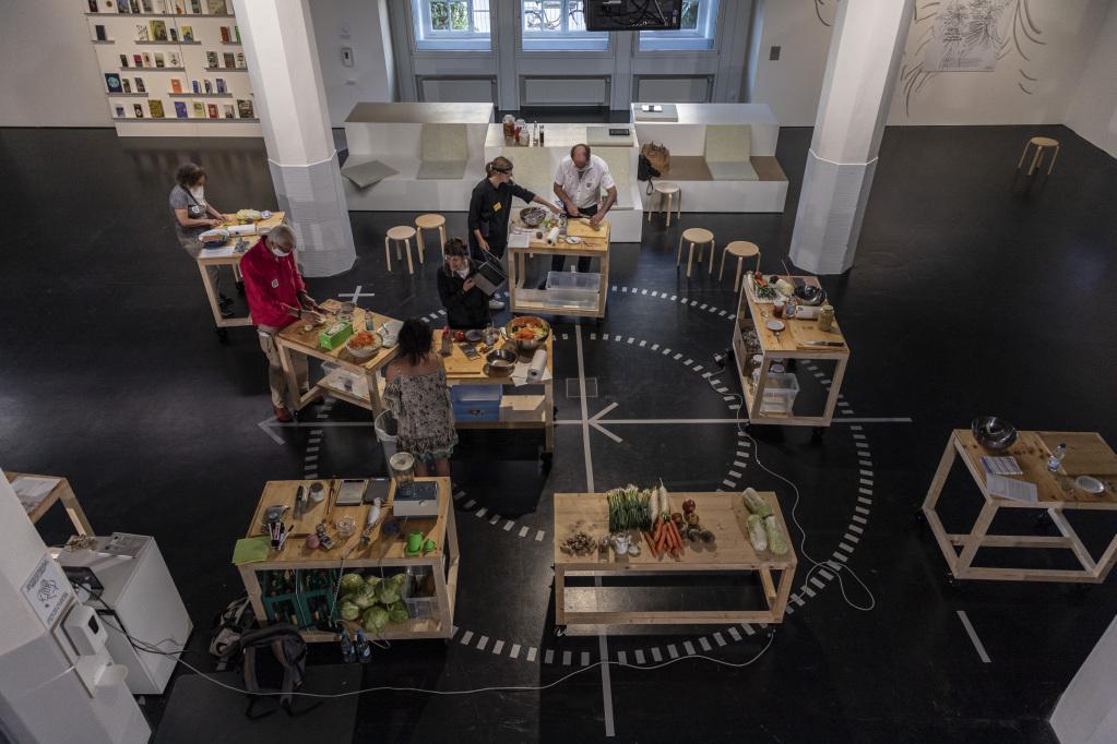Gemüse und Küchenutensilien auf Holztisch, fotografiert aus der Vogelperspektive.