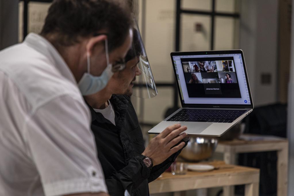 Ein Mann hält seinen Laptop hoch und zeigt anderen Teilnehmer:innen in einer Videokonferenz, was der Mann neben ihm vor sich hat.
