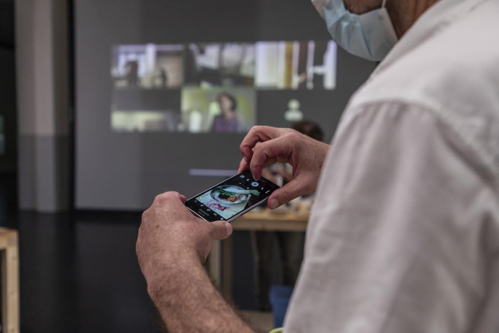 Eine Person fotografiert einen Teller mit Essen auf ihrem Smartphone. Im Hintergrund wird eine Videokonferenz auf die Wand projiziert