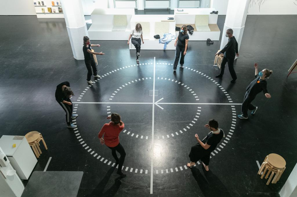 Eine Gruppe Menschen steht im Kreis auf einem runden Diagramm auf einem Hallenboden. Die Menschen scheinen in Bewegung zu sein.