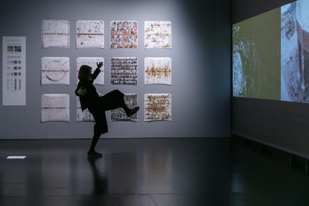 Ein Mensch steht gestikulierend und auf einem Bein vor einer Projektion an der Wand. Im Hintergrund sind einige aufgehängt Bilder an der Wand zu sehen