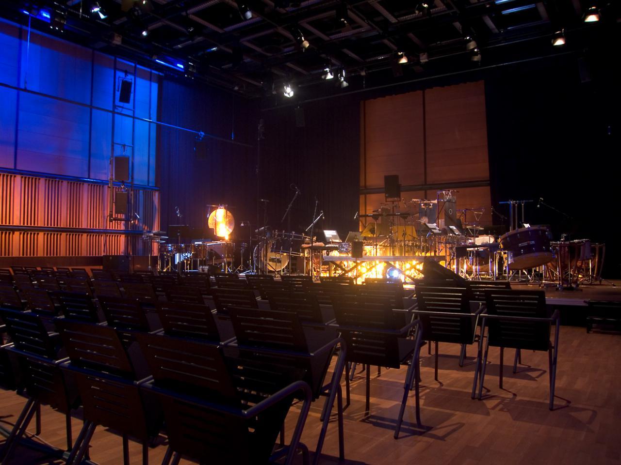 Leere Reihenbestuhlung im ZKM_Kubus mit Orchesteraufbau auf der Bühne