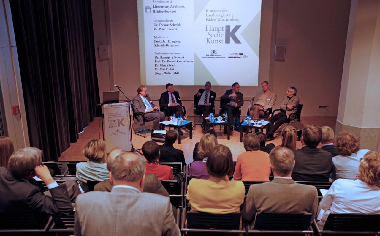 Besetzter ZKM_Vortragssaal mit Blick auf Teilnehmer der Podiumsdiskussion
