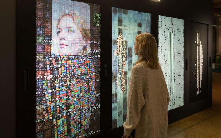 A woman stands in front of a wall with several screens and digital representations