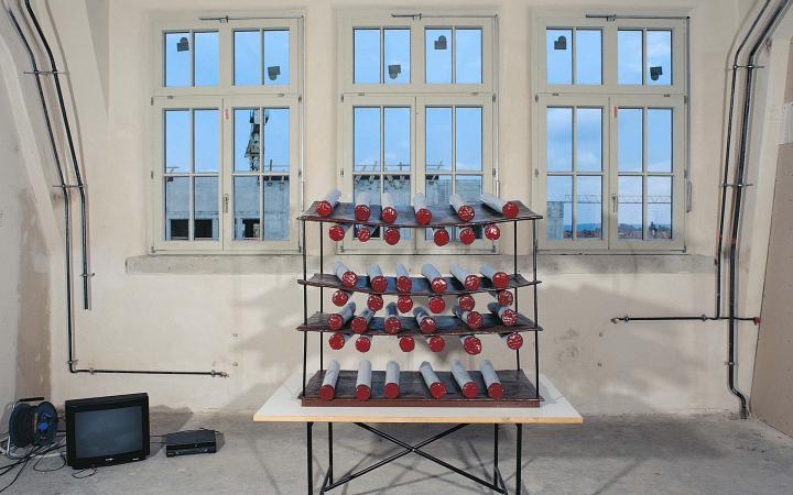 Ein Raketenwerfer auf einem Eiermann-Tisch zielt auf eine Fensterfront. Dahinter ist ein Rohbau zu sehen.