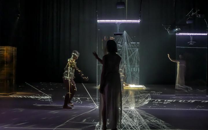 Three dancers stand on the stage, it is dark. In the middle of the stage is an installation of laser light. On the body of the left dancer is a projected play of light.