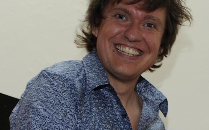 Ein lachender Mann, der ein blaues Hemd trägt.