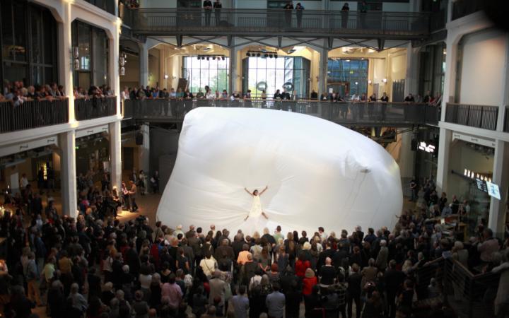Ein riesiger Ballon, auf dem eine Frau schwebt. Drum herum viele Menschen