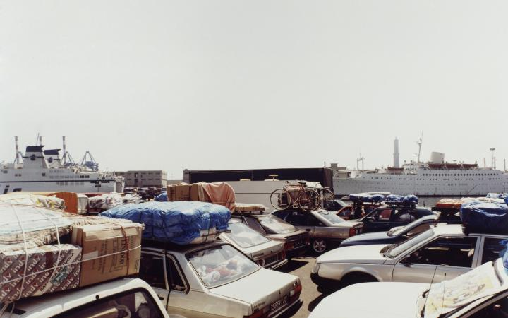 Photography of several parked cars, all fully loaded. In the background are two large cruise ships.