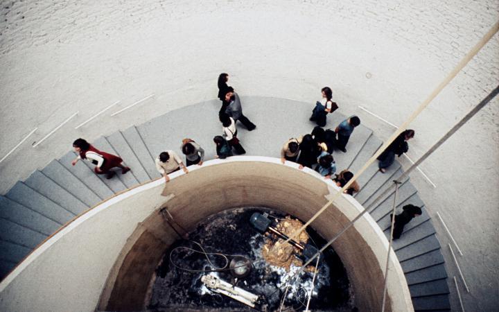 Menschen laufen eine Treppe herunter zu einer Pumpanlage