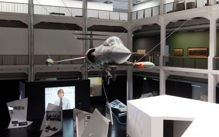 Flugzeug hängt an Seilen in einem Lichthof
