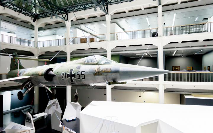 A starfighter which is hanging from the ceiling in the museum