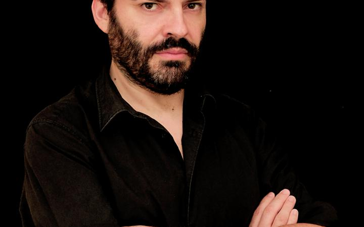 Ein Mann in schwarzem Hemd mit verschränkten Armen