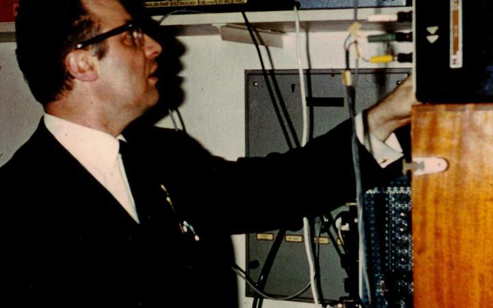 Ein Mann im schwarzen Anzug und schwarzer Hornbrille bedient diverse elektronische Gerätschaften.