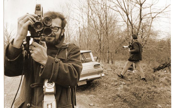 Ein schwarz-weiß Bild von einem Mann, der ebenfalls fotografiert. Im Hintergrund steht ein Auto und ein weiterer Mann läuft in das Bild