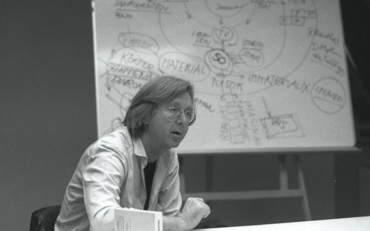 Black and white photograph of a man sitting at a table. In the background a flip chart.