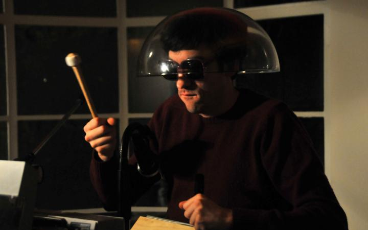 A man wearing sunglasses and transparent lampshade on his head, holding a drumstick in his right hand.