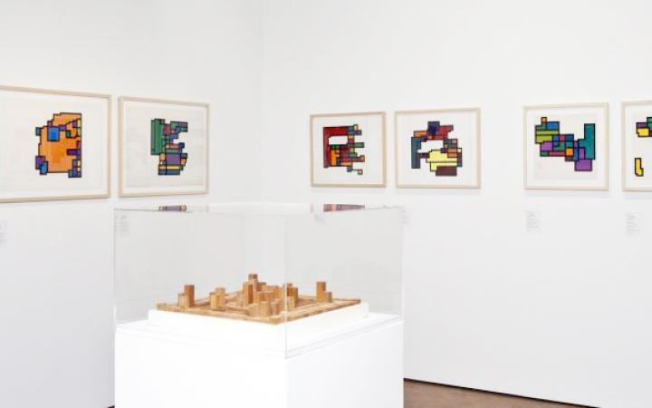 A view of the exhibition »Hiroshi Kawano«: A room with seven paintings with geometric patterns, in the middle an abstract wooden sculpture.