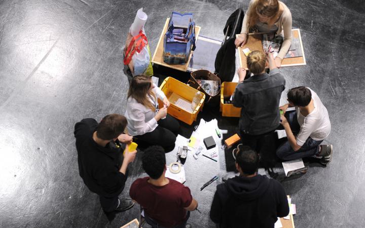 Eine Gruppe von Schülern sitzt auf dem Boden und bastelt.