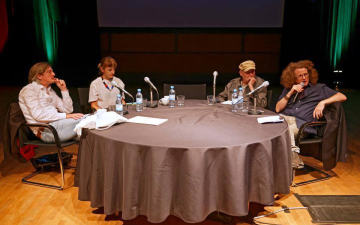 Vier Personen an einem Tisch mit Mikrophonen