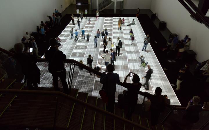 Menschen laufen auf einer großen Projektion