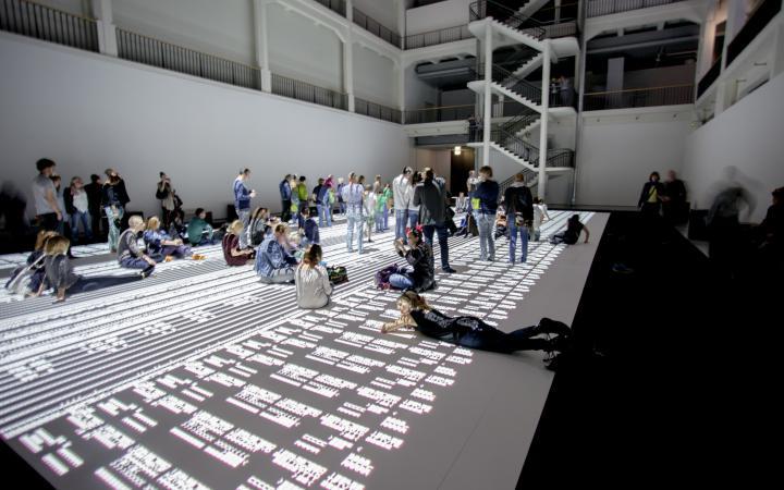 Menschen sitzen, liegen und stehen auf einer großen Projektion