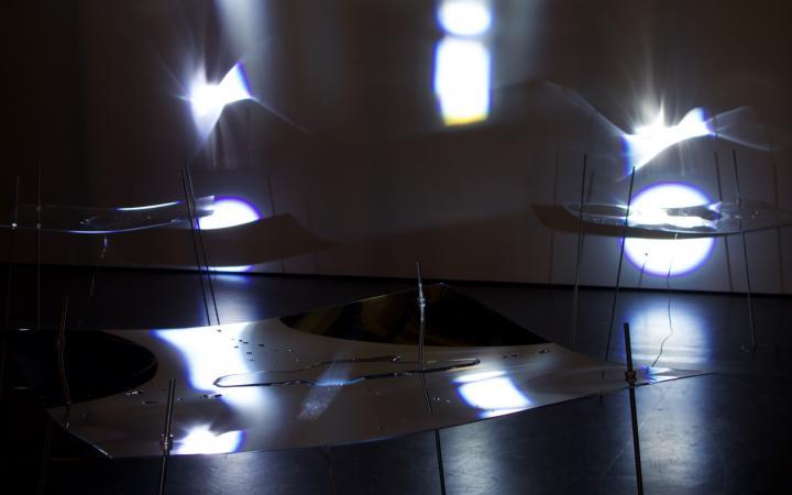 Ein dunkler Raum mit zarten Strukturen aus Plexiglas und Flüssigkeit, auf die Licht fällt.