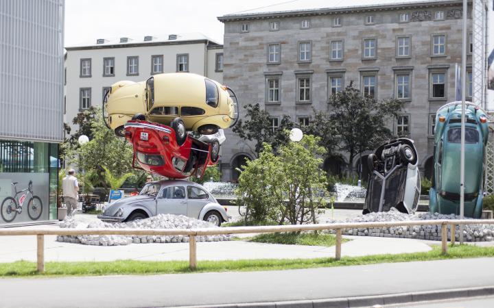 VW-Käfer in verschiedenen Farben übereinander gestapelt